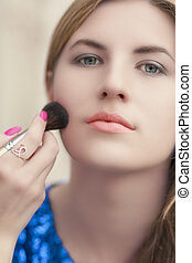 portrait of young blond woman doing brush makeup