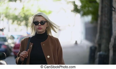 Portrait of young blonde businesswoman goes to work or date in autumn city. Girl have stylish look, sunglasses and nose piercing. Lady walking on the street alone. Fashion concept