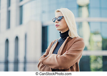Portrait of young blonde businesswoman in autumn city. Girl have stylish look, sunglasses and nose piercing. Lady walking on the street alone. Fashion concept.