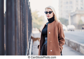 Portrait of young blonde businesswoman in autumn city. Girl have stylish look, sunglasses and nose piercing. Lady walking on the street alone. Fashion concept