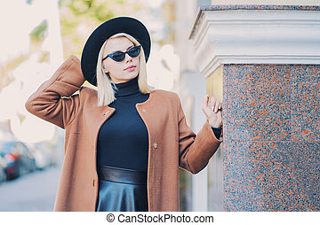 Portrait of young blonde hipster woman in hat in autumn city. Girl have stylish look, sunglasses and nose piercing. Lady walking on the street alone. Fashion concept.