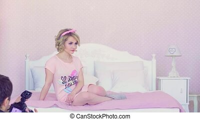 Portrait of young blonde model posing in the bed