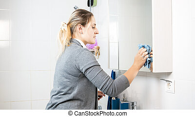 Portrait of young blonde woman cleaning bathroom with rag -...