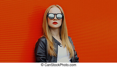 Portrait of young blonde woman in sunglasses on a red background
