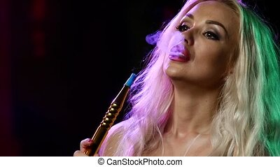 portrait of young blonde woman in the hookah room. Slow motion. Close up