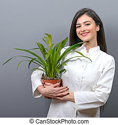 Portrait of young botanist woman in uniform holding plant against gray background