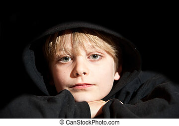 Portrait of young boy aged nine years old in black hoodie -...