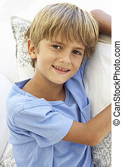 Portrait Of Young Boy Relaxing On Sofa