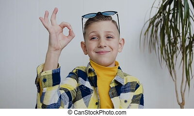 Portrait of young boy with blue eyes who looking at the camera smiles and shows with his hand that everything is Okay. Little blonde boy looking at camera over white background, in indoor