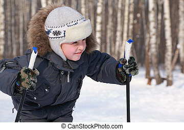Portrait of young boy with ski poles looking to side inside winter forest at sunny day