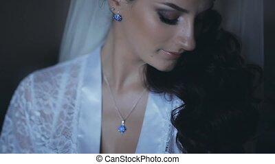 Portrait of young brunette bride wearing elegant white...