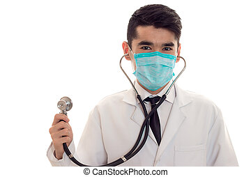 portrait of young brunette man doctor i mask with stethoscope looking at the camera isolated on white background