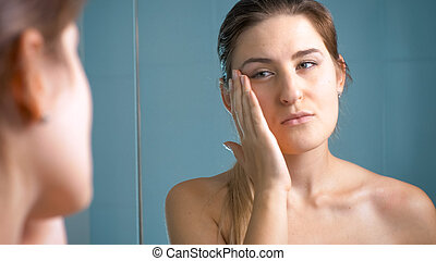 Portrait of young brunette woman checking her skin after bathing