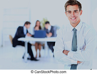 Portrait of young business man smiling with colleagues in background.