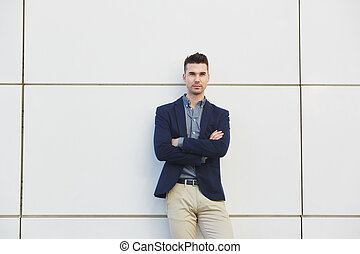 young business man standing against white wall with arms crossed