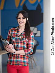 portrait of young business woman at office with team in background