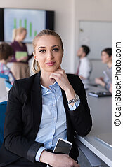 portrait of young business woman at office with team on meeting in background