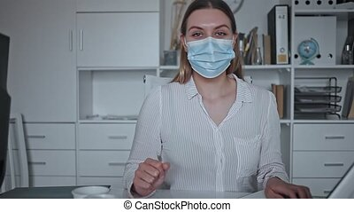 Portrait of young business woman in medical face mask talking at camera in office. Concept of precautions and social distancing in COVID 19 pandemic