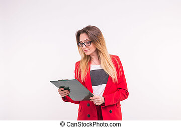 Portrait of young business woman in red jacket with paper clip in hands.
