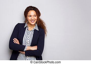 young business woman smiling against gray background