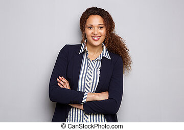 young business woman with curly hair smiling against gray wall