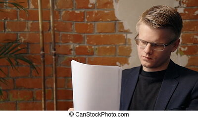 Portrait of young businessman in glasses reading paper...