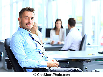 Portrait of young businessman in office with colleagues in ...
