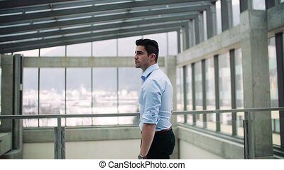 Portrait of young businessman indoors in an office. Slow...