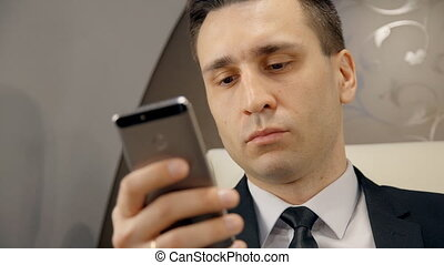 Portrait of young businessman is using smartphone sitting in...