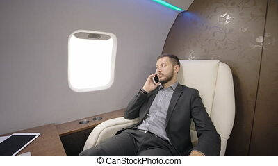 Portrait of young businessman lawyer talking on phone in luxury private jet.
