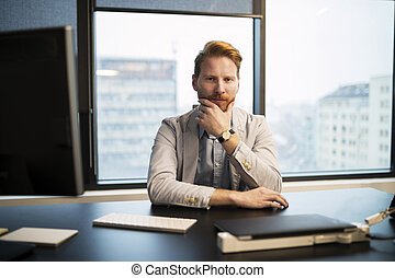 Portrait of young businessman sitting at desk