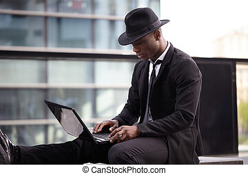 Portrait of young businessman sitting outside with laptop
