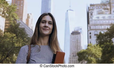Portrait of young businesswoman holding the documents. Female looking at camera and gives the thumbs-up in New York, USA