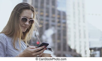 Portrait of young businesswoman in sunglasses using the smartphone, holding the coffee cup on the street during break.