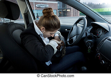 businesswoman sitting on drivers seat and looking inside handbag
