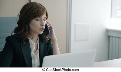 Portrait of young businesswoman talking on phone in her...