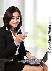 young businesswoman using mobile phone while working in the offi