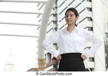 Photo of young businesswoman with arms akimbo