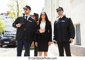 Portrait Of Young Businesswoman With Bodyguards