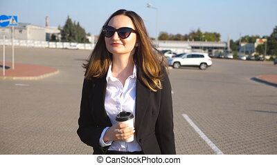 Portrait of young businesswoman with cup of coffee walking...