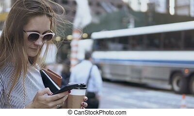 Portrait of young busy businesswoman holding the coffee cup and documents and using the smartphone on the street.