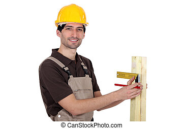 portrait of young carpenter taking measurements