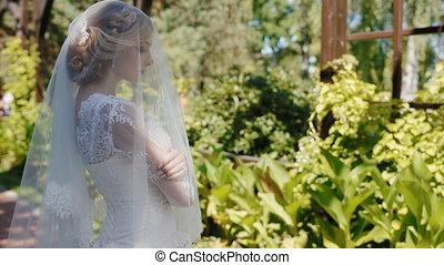 Portrait of young caucasian bride in the garden