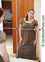 Portrait of young Caucasian female in dress standing against mirror and looking at herself in domestic room