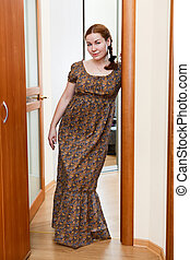 Portrait of young Caucasian female in dress standing in domestic room