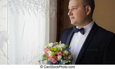 Portrait of young caucasian man with wed bouquet