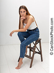 portrait of young caucasian pretty woman with long hair in corset and blue jeans