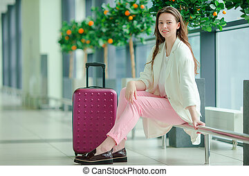 Portrait of young caucasian woman an airport waiting for her aircraft