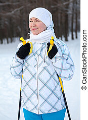 Portrait of young Caucasian woman skier standing on skis with ski poles