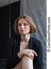 portrait of young caucasian woman with short hair posing in black suit jacket